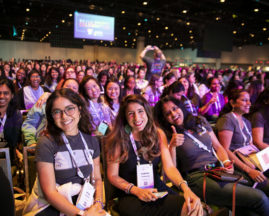 Audience members smile at the GHC 19 Opening Keynote