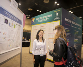A poster presenter talks about her research to another young woman at GHC 19
